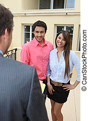 Estate-agent with young couple