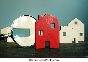 Estimating the value of real estate. Small house and magnifying glass.