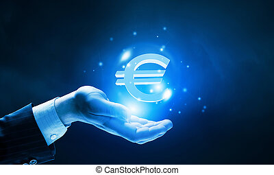 Close up of human hand holding golden euro symbol