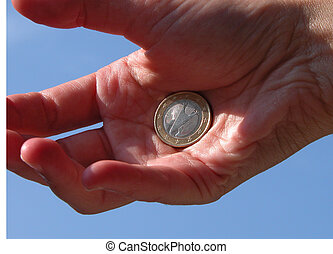 a backside of an euro coin in a hand and the sky is background