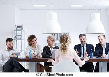 Examination board interviewing woman