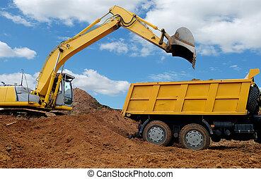 Excavator loading dumper truck tipper in sand pit over blue sky