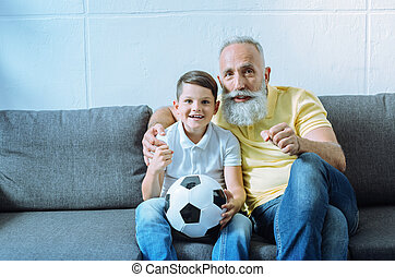 Excited grandchild and senior man watching football match