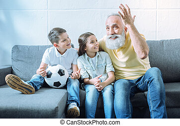 Excited grandfather telling children interesting story