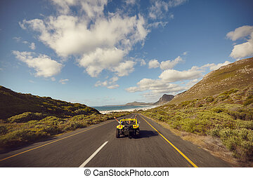 Excited young couple driving down on a open road