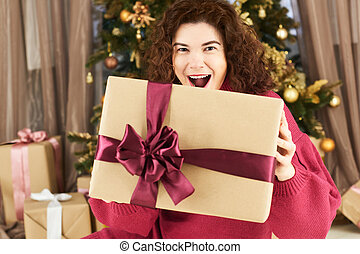 exciting young woman holding christmas gift in front of face on new year tree background