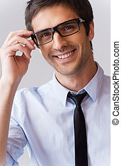 Expert look. Portrait of handsome young man in shirt and tie adjusting his eyeglasses and smiling while standing against grey background