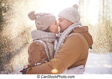 Young dates in winterwear kissing in snowfall
