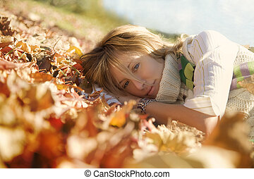 expressing positivity: blond girl resting on autumn leaves