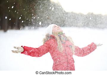 Portrait of beautiful woman taking pleasure on snowy winter day