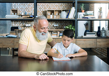 Extremely happy elderly man looking at grandchild doing his homework