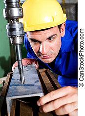 worker using industrial drilling machine