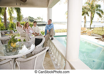 Portrait of family on vacation relaxing on terrace together