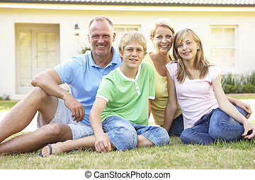 Family Sitting Outside Dream Home