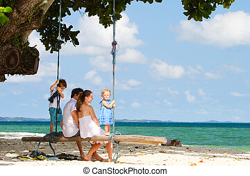 Family swinging on tropical beach