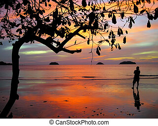 Fantastic Sunset and silhouette of a man on the beach