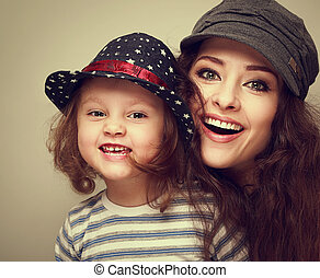 Fashion mother and kid girl happy toothy laughing in trendy caps. Vintage closeup portrait