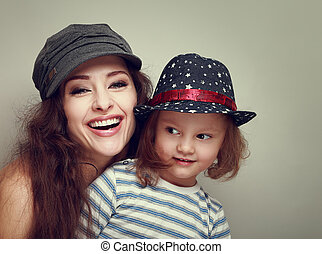 Fashion smiling family in caps. Laughing mother and fun kid girl. Vintage portrait