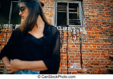 Fashionable cool woman in black sunglasses and denim jeans standing at old brick building, focus on wall. Stylish hipster girl posing in street, atmospheric moment. Space text.