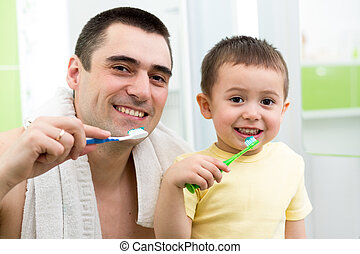 father and child boy brushing teeth before going to bed