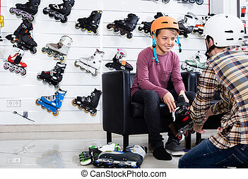 Father helping to his child to stand up at new rollers
