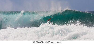 A fearless surfer is riding a huge wave on the beautiful Hawaii Oahu's North Shore