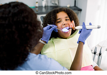Female African dentist performing dental filling procedure to a little mixed raced school girl in pediatric dental clinic. Doctor using dental ultraviolet curing light for filling polymerization