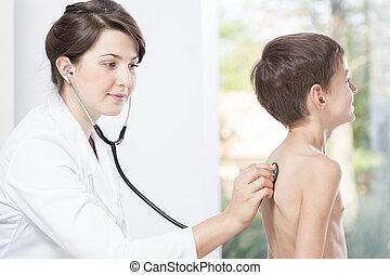 Female doctor examining little boy