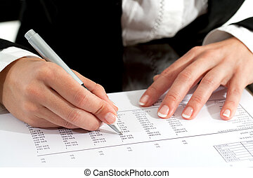 Female hands with pen reviewing document.