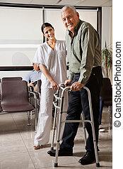 Female Nurse Helping Senior Patient With Walker