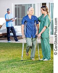 Female Nurse Helping Senior Woman To Use Crutches