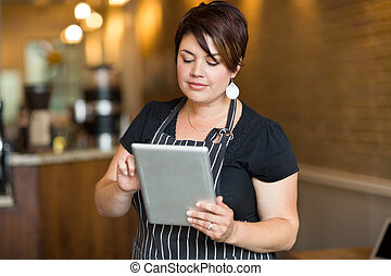 Female Owner Using Digital Tablet In Cafe
