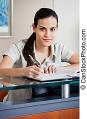 Female Receptionist Writing In Book
