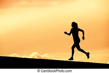 Female runner silhouette, running into sunset