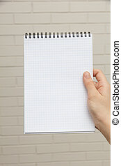 female teen hand holding notepad