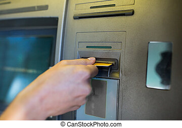 close up of hand inserting card to atm machine