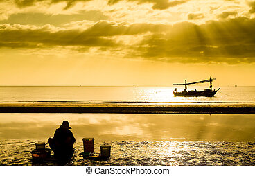 Fisher on beach and boat on sunset