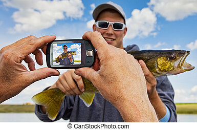 A proud fisherman posing with his catch having his picture taken