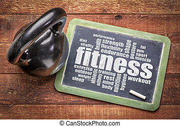 fitness word cloud on blackboard with a kettlebell