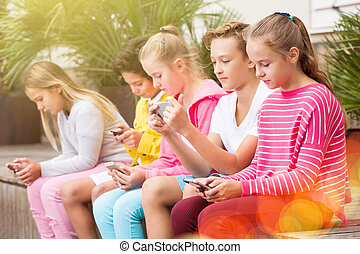 Five kidsare chatting on their smartphone