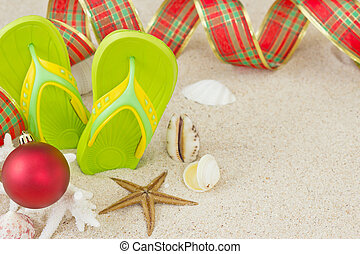 Flip Flops in the sand with shells and Christmas decoration. Xmas summertime on beach concept.