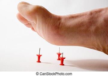 Foot stepping on tacks