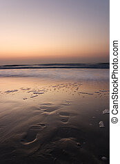 Footprints leading into water on beach at sunset