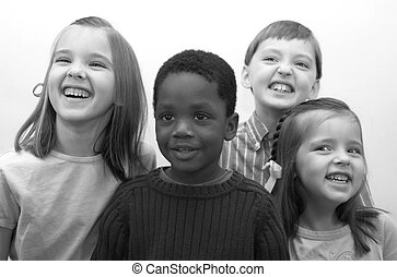 Four beautiful children smiling for the camera.