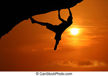 Free climbing on the mountain at red sky sunset background
