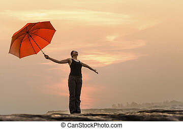 Free Happy Woman Enjoying Nature. Beauty Girl Outdoor. Freedom concept. Beauty Girl over Sky and Sun with umbrella
