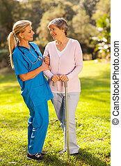 friendly caregiver talking to senior woman outdoors