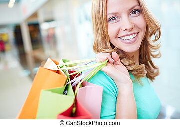Portrait of happy girl with shopping bags looking at camera
