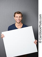 Friendly handsome young man with a blank sign