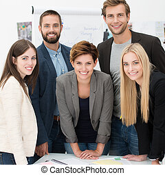 Friendly successful business team of multiethnic young executives standing together posing for the camera and smiling